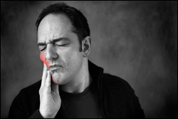 middle-aged man holding his cheek from tooth pain