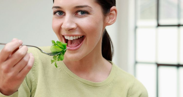 young woman eating a bowl of leafy greens and smiling