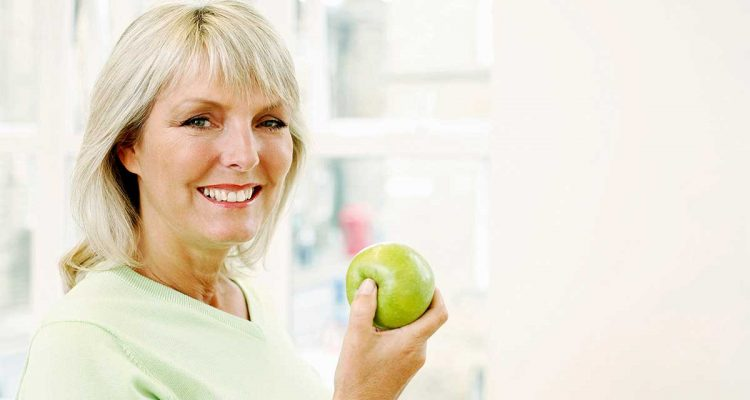 older woman holding a green apple and smiling