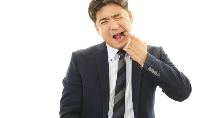man in a business suit wincing and reaching into his mouth